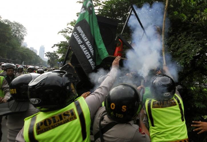 A police officer fires his tear gas launcher in a brief clash with students during a protest against Israel's attack on Gaza, outside the U.S. Embassy in Jakarta, Indonesia, Wednesday, Nov.21, 2012. (AP Photo)