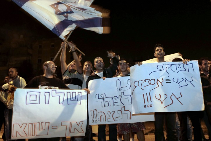 """Israelis hold signs and flags as they protest the cease-fire in the southern Israeli city of  Kiryat Malachi.  Hebrew on signs from right read: """"Cease-fire = supply of fire"""", """"Let the IDF win"""" and """"False peace"""". Nov. 21 2012(AP Photo/Tsafrir Abayov, File)"""