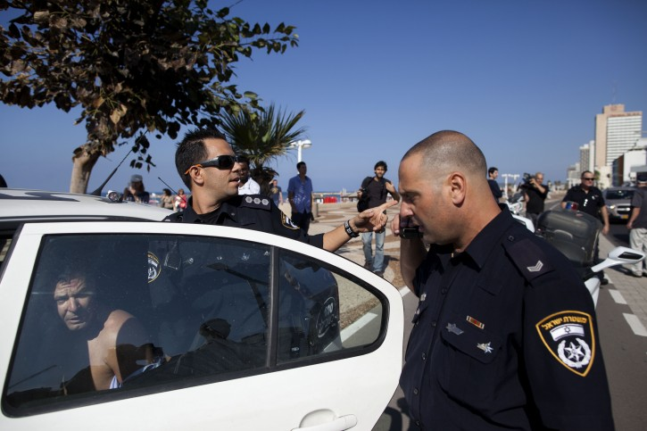 Israeli police officers detain a man who attacked a security guard at the U.S. embassy in Tel Aviv, Israel, Tuesday, Nov. 20, 2012. (AP Photo/Oded Balilty)