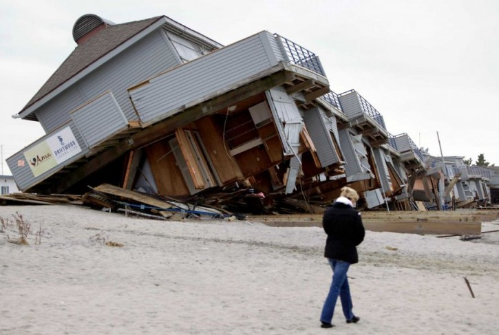 A woman walks past a cabana complex on the beach pulled off its foundations by Superstorm Sandy in Sea Bright, N.J., Monday, Nov. 19, 2012.</p>  <p>PHOTO BY SETH WENIG/ASSOCIATED PRESS