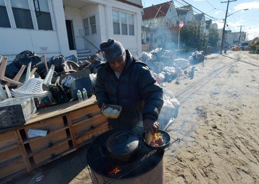 Collins Wimbish cooks food over a fire in a barrel in the Rockaways neighborhood of Queens, New York, USA, 03 November 2012. Large areas of the city are still without power or functioning stores to buy food and water following Hurricane Sandy.  EPA/JUSTIN LANE