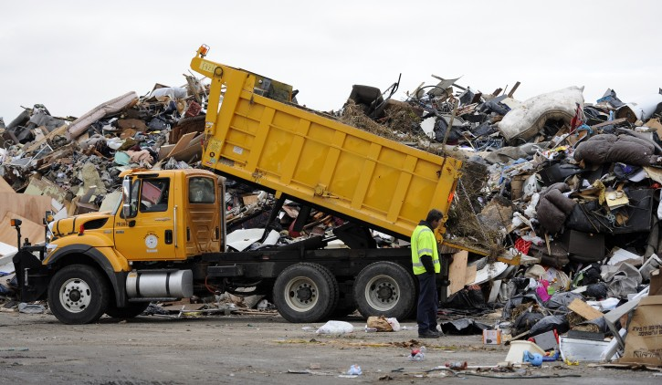 A worker directs a truckload of debris and garbage from damaged homes at a makeshift dump in a parking lot as the area continues to deal with the aftermath of Hurricane Sandy in Lido Beach, New York, USA, on 13 November 2012.  EPA/ANDREW GOMBERT