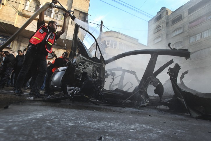 Emergency services extinguish the burned out destroyed car of Qassam top leader Ahmed Jabari after an Israeli air strike in Gaza City on 14 November 2012. Hamas says the head of its military wing has been killed in an Israeli air strike. Israel said it had targeted Ahmed al-Jabari because of what it called his decade-long terrorist activity.  EPA/ALI ALI