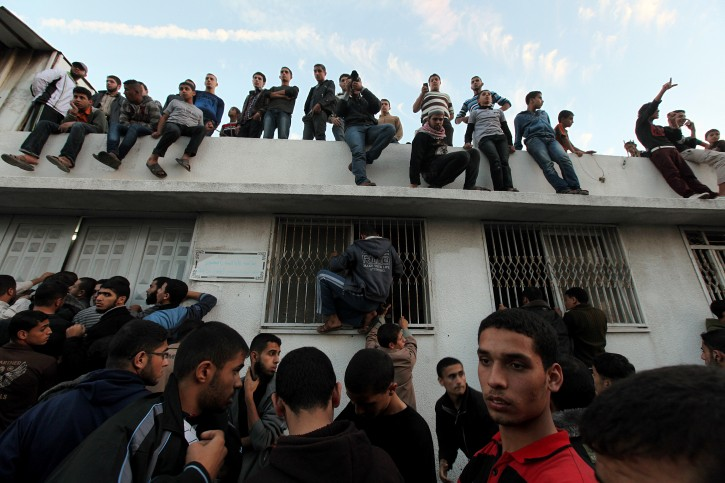 People stand outside and on the roof of the morgue at Al-Shifa hospital with the body of Qassam top leader Ahmed Jabari inside after an Israeli air strike in Gaza City, 14 November 2012. Ahmed Ja'abari was killed when the car in which he was driving was hit in an Israeli air strike. Another militant, whose identity was not immediately known, was killed alongside him. His death came after four days of Israeli-Palestinian violence, which saw militants in the Strip launch over 120 rockets at southern Israel, and the Israeli Air Force hit 15 targets in the enclave.  EPA/MOHAMMED SABER
