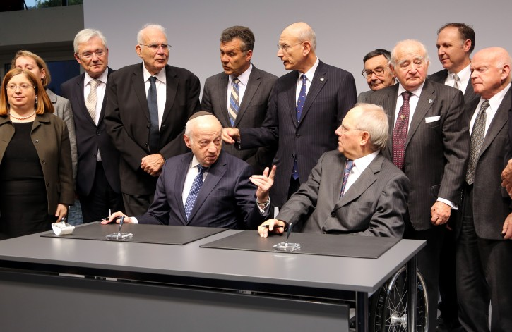 German Finance Minister Wolfgang Schaeuble and Chairman of the Jewish Claims Conference Julius Berman (C-L) signs the new article 2 agreement for compensation to the victims of the Nazis during a ceremony for the 60th anniversary of the Reparations Agreement between Israel and West Germany at the Jewish Museum in Berlin, Germany, 15 November 2012. The new agreement simplifies the previous regulations and allows reparations to victims, mainly in eastern Europe, who have not received compensation.  EPA/WOLFGANG KUMM