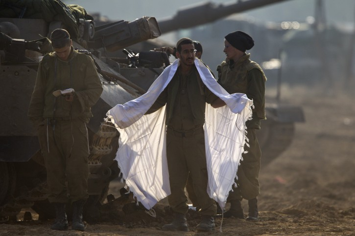 An Israeli soldier prepares for morning prayers at his APC (Armoured Personnel Carrier) on a tank staging area in southern Israel along the border with the Gaza Strip, 19 November 2012. Behind, a group of religious soldier take part in morning prayers. Reports state that the Israeli military is prepared to significantly widen operations against Palestinian militants in the Gaza Strip. EPA