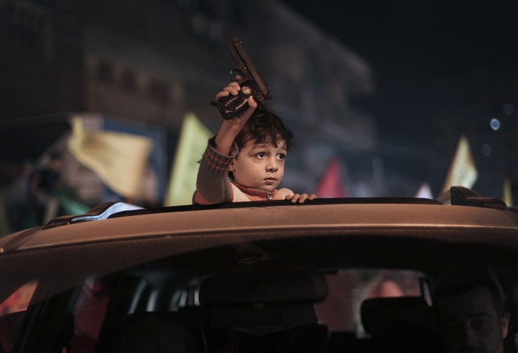 A child holds a gun as Palestinians celebrate a ceasefire agreement between Israel and Gaza in Gaza City, 21 November 2012. EPA/ALI ALI