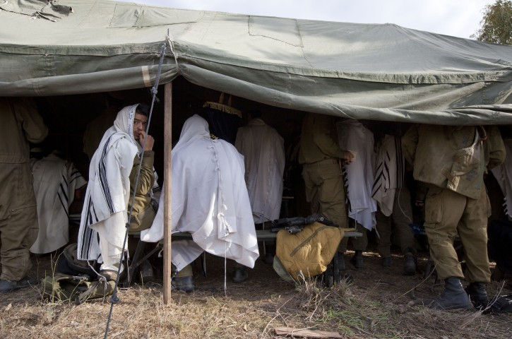 Israeli soldiers under a tent at a staging area in southern Israel finish morning prayers along the border with the Gaza Strip, 22 November 2012. EPA/JIM HOLLANDER