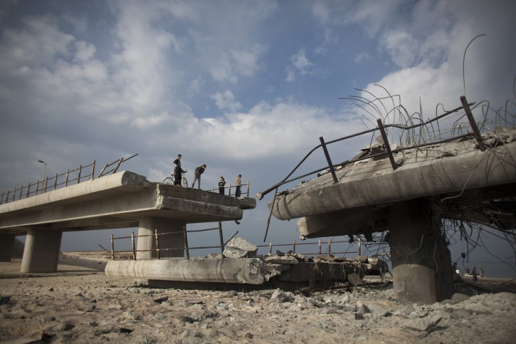 Palestinians check the extend of damage of a destroyed bridge connecting the northern and central part of the Gaza Strip, near Gaza City, 22 November 2012. EPA/OLIVER WEIKEN