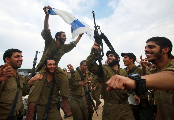 Israeli infantry soldiers in a staging area on the Gaza Strip border celebrate the ceasefire between Israel and Hamas, brokered by Egypt and the United Staes, which brought eight days of intensive fighting to a halt, in southern Israel, 22 November 2012. Israeli ground forces did not enter Gaza.  EPA/MIRI TSACHIE  EPA/MIRI TSACHIE ISRAEL