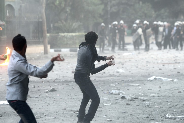 Egyptian supporters and opponents of President Mohamed Morsi throw stone at anti-riot securrity forces during clashes following a rally over Morsi decrees, in tahrir square, Cairo, Egypt, 23 November 2012.  Supporters and opponents of President Mohamed Morsi rallied across Egypt on 23 November, one day after the Islamist leader passed decrees giving himself sweeping new powers. As Morsi was speaking on 23 November, police clashed with protesters near Tahrir Square where thousands of his opponents converged, demanding a reversal of the constitutional declaration.  EPA/KHALED ELFIQI
