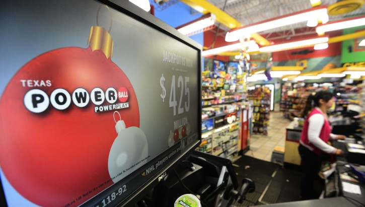 Alma Villaseno (R) helps customers at a Valero gas station in Dallas, Texas, USA, 27 November 2012. The Powerball drawing on 28 November, was boosted today to $500M EPA/LARRY W. SMITH