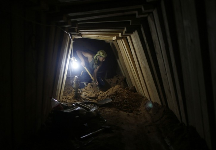 A Palestinian worker shovels sand as he repairs a damaged smuggling tunnel dug beneath the Egyptian-Gaza border in Rafah, in the southern Gaza Strip on November 26, 2012. (Mohammed Salem / Reuters)