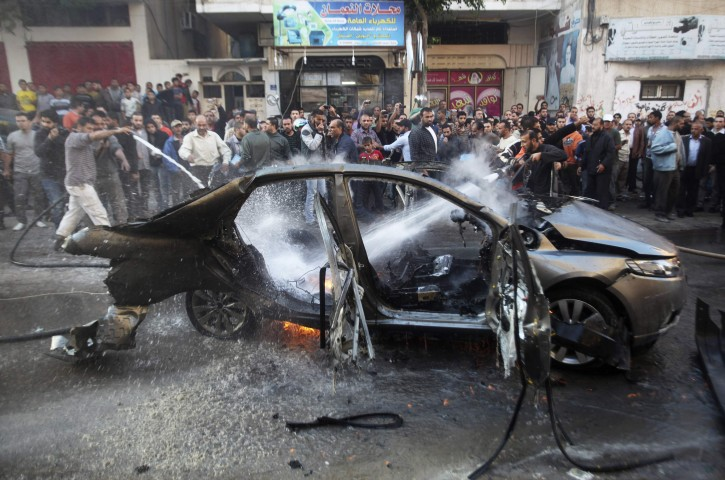 Palestinians extinguish a fire after an Israeli air strike on a car in Gaza City November 14, 2012. Hamas's military chief was killed when his car was hit by an Israeli airstrike on Wednesday, the Palestinian Islamist group said, with multiple Israeli attacks rocking the Gaza Strip. Hamas said Ahmed Al-Jaabari, who ran the organisation's armed wing, the Izz el-Deen Al-Qassam, died along with a passenger after their car was targeted by an Israeli missile.  REUTERS/Ali Hassan