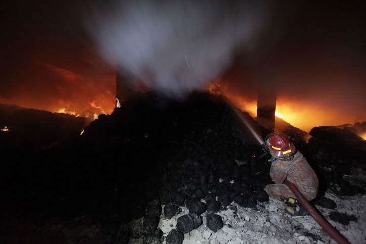 A firefighter tries to control a fire at a garment factory in Savar, outskirts of Dhaka November 24, 2012. At least 120 died and over 100 were injured as a fire broke out at Tazreen Fashions Limited in Savar on Saturday evening, police said.  REUTERS/Andrew Biraj