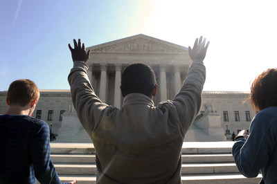 FILE - Advocates raises their hands in prayer outside the Supreme Court in Washington DC. EPA