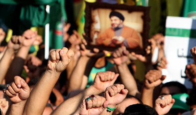 FILE - Supporters of Hezbollah hold a picture depicting hezbollah leader Hassan Nasrallah are they raise their hands and chant slogan of 'God is Great', during a mass rally in southern City port of Tyre, Lebanon, 19 September 2012.