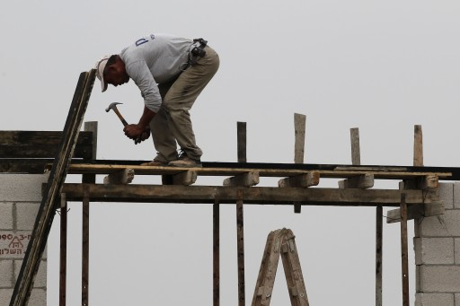 FILE - Palestinian construction worker work on the expansion of the Jewish settlement of Tzufim near the West Bank town of Qalqilya on October 31, 2012.  flash90