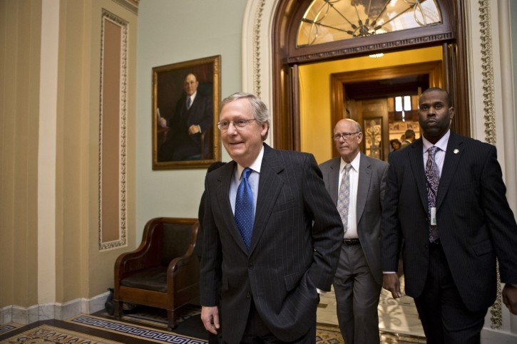 Senate Minority Leader Mitch McConnell, R-Ky., followed by Sen. Pat Roberts, R-Kan., second from right, leaves the Senate chamber to meet with fellow Republicans in a closed-door session as the