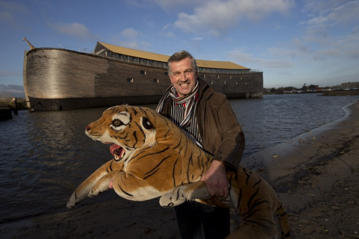 Johan Huibers poses with a stuffed tiger in front of the full scale replica of Noah's Ark after being asked by a photographer to go outside with the animal in Dordrecht, Netherlands, Monday Dec. 10, 2012. (AP Photo/Peter Dejong)