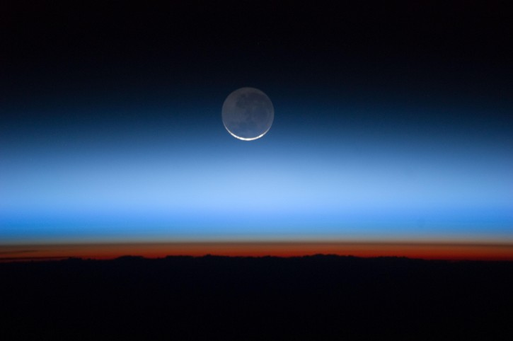 Image made available by NASA shows the moon, at center with the limb of Earth near the bottom transitioning into the orange-colored troposphere, the lowest and most dense portion of the Earth's atmosphere. (AP Photo/NASA)
