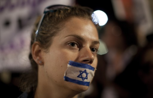 An Israeli women has her countries flag fixed over her mouth during a protest in Tel Aviv over corruption. EPA/OLIVER WEIKEN
