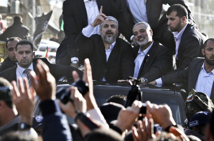 Hamas leader Khaled Meshaal (C) Hamas Prime Minister, Ismail Haniyeh (C-R) wave from the rooftop of a vehicle following Meshaal's arrival through the Egyptian-Gaza border in Rafah, Gaza Strip, 07 December 2012. EPA/ALI ALI
