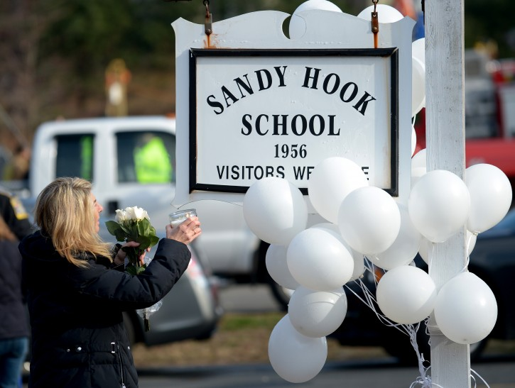 Andrea Jaeger holds a candle up at a memorial following a shooting  on 14 December that left at least 28 people dead, 20 of them young children, in Newtown, Connecticut, USA, 15 December 2012.  Reports state on 14 December 2012 that a gunman unleashed a hail of gunfire that killed 20 children and six adults at a school in Newtown, a quiet, affluent suburb of 27,500 people about 100 kilometres north-east of New York City. He then killed himself inside Sandy Hook Elementary School, having previously killed his mother.  EPA/JUSTIN LANE