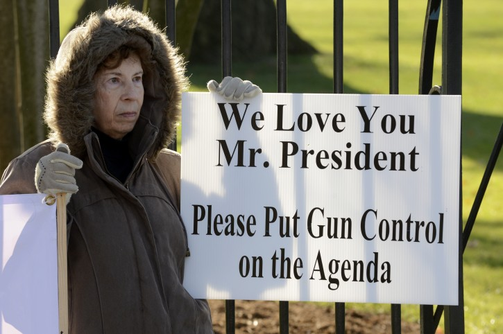 A supporter of gun control holds a sign that reads, 'We Love You Mr. President, Please Put Gun Control on the Agenda' outside the White House in Washington DC, USA, 15 December 2012.  Reports state on 14 December 2012 that a gunman unleashed a hail of gunfire that killed 20 children and six adults at a school in Newtown, a quiet, affluent suburb of 27,500 people about 100 kilometres north-east of New York City. He then killed himself inside Sandy Hook Elementary School, having previously killed his mother.  EPA/MICHAEL REYNOLDS