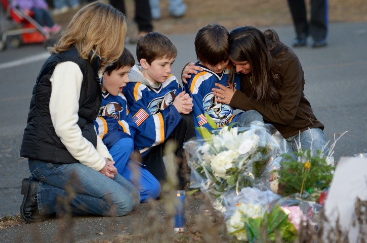 People pause near a memorial down the street from the Sandy Hook Elementary School following a shooting at on Friday that left 26 people dead, 20 of them young children, in Newtown, Connecticut, USA, 15 December 2012.  EPA/JUSTIN LANE