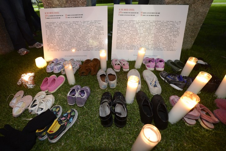 Candles are placed next to children's shoes representing the 20 first graders (6-7 years old) that were killed in the Sandy Hook Elementary School massacre in Connecticut in Los Angeles, California, USA, 15 December 2012. In additon to the 20 school children killed, six adults were also gunned down in the second worse school shooting in US history.  EPA/MICHAEL NELSON