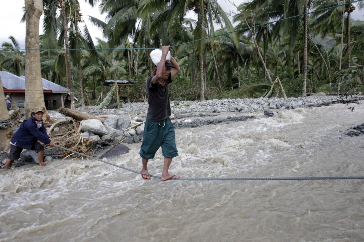 A villager walks on rope over floodwaters that flows down a destroyed road caused by typhoon Bopha in Compostela Valley, southern Philippines December 5, 2012. REUTERS/Erik De Castro