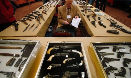 Antique gun collector Dave Kleiner reviews paperwork during the East Coast Fine Arms Show in Stamford, Connecticut, January 5, 2013. (REUTERS/Carlo Allegri)