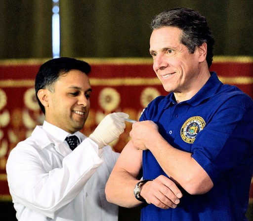Gov. Andrew Cuomo (right) gets a flu shot from state Health Commissioner Nirav Shah Thursday in the Red Room of the Capitol in Albany. Gov. Cuomo hopes to raise awareness about a severe flu outbreak this year. (Skip Dickstein / The Albany Times Union, via AP)