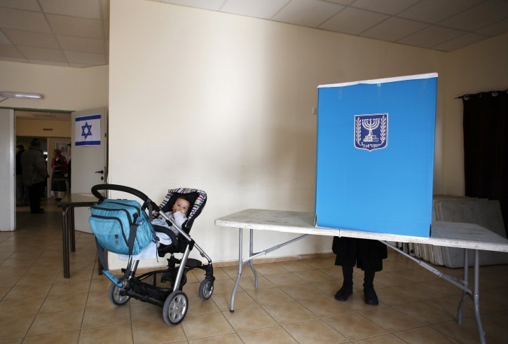 A baby waits in a pram as her mother casts her ballot for parliamentary elections at a polling station in the West Bank Jewish settlement of Elon Moreh, near Nablus January 22, 2013. REUTERS/Baz Ratner