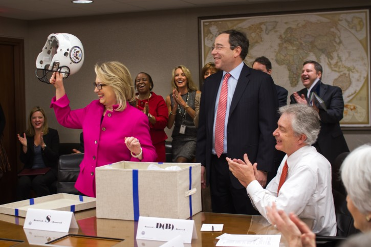 This photo provided by the United States Department of State shows Secretary of State Hillary Rodham Clinton holding up a football helmet presented to her at the State Department in Washington, Monday, Jan. 7, 2013. (AP Photo/United States Department of State)