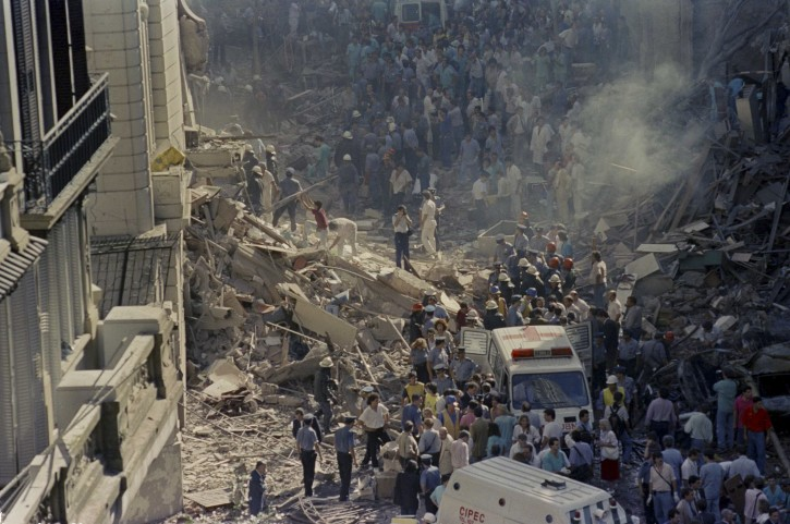 In this March 17, 1992 file photo, firemen and rescue workers walk through the debris of Israel's Embassy after a terrorist attack in Buenos Aires, Argentina. (AP Photo/Don Rypka, File )