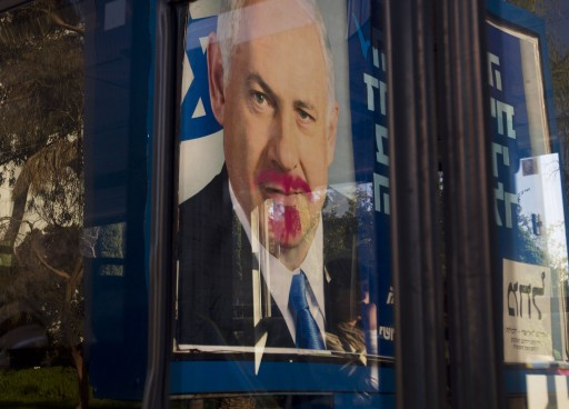 A vandalized election campaign billboard of Israeli Prime Minister and Likud Party leader Benjamin Netanyahu is reflected on a bus window in Tel Aviv, Israel, Monday, Jan. 21, 2013. (AP Photo/Ariel Schalit)