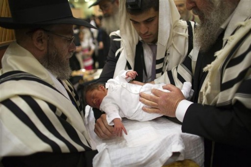 FILE - An ultra-Orthodox Jewish father (C) holds his son before his circumcision September 24, 2012.  Reuters