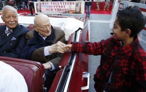 FILE 0 Former mayor of New York and Grand Marshal of the parade Ed Koch shakes hands with a boy at the start of the parade as former mayor David Dinkins (L) looks on during the Veterans Day Parade in New York November 11, 2012. REUTERS/Carlo Allegri