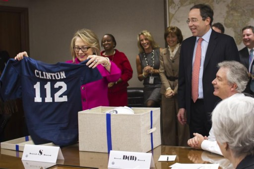 "U.S. Secretary of State Hillary Clinton holds up a football jersey with her name on it,  presented by Deputy Secretary of State Thomas Nides (2ndR), who joked that ""Washington is a contact sport,""  during a weekly meeting of assistant Secretaries of State, in this handout photograph taken and released by the State Department on January 7, 2013. Clinton resumed her official duties on Monday, five days after being released from a hospital for treatment of a blood clot. The number 112 refers to the number of countries that Clinton has visited as secretary of state. REUTERS/State Department/Nick Merrill/Handout"
