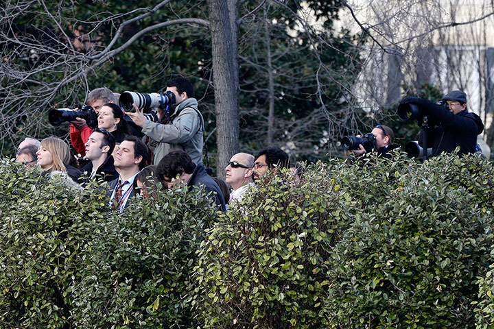 Washington DC: Reporters and photographers watch congressional leaders from afar as they arrive at the White House for a closed-door meeting with Barack Obama on the fiscal cliff. Photograph: Charles Dharapak/AP