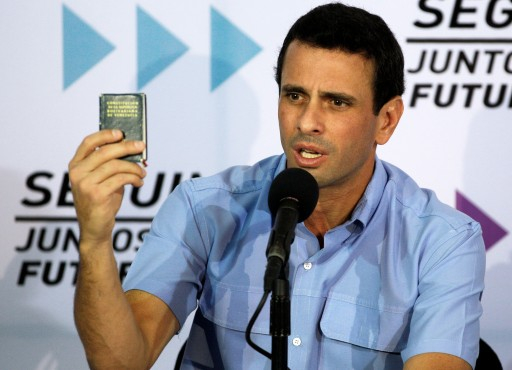 Venezuela's opposition leader Henrique Capriles holds up a miniature copy of the national constitution during a news conference in Caracas, Venezuela, Tuesday, Jan. 8, 2013. (AP Photo/Fernando Llano)