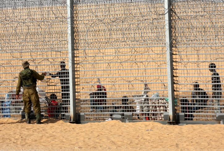 An Israeli solders passes a bottle of water through a border fence to an African migrant. EPA/Yehuda Lahiani ISRAEL OUT