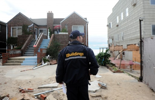 A Department of Buildings inspector looks over homes damaged during Hurricane Sandy in Sea Gate part of Brooklyn. EPA/ANDREW GOMBERT