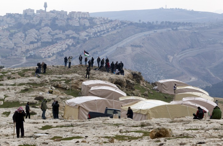 A Bedouin man (L) leaving what Palestinians call the new 'outpost settlement' of Bab al-Shams (Gate of the Sun), 11 January 2013, set-up outside the Palestinian West Bank village of Ez Za'im in the contentious area east of Jerusalem, in the West Bank known as E1, overlooking the sprawling Jewish settlement of Ma'ale Adumim, partially seen behind. EPA/JIM HOLLANDER