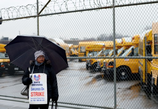 A school bus driver stands in a picket line outside of a bus depot on the first day of a strike in Jamaica, New York, USA, 16 January 2013. The school bus drivers union, Amalgamated Transit Union Local 1181, are striking due to a dispute with the city over seniority-based job protection.  EPA/JUSTIN LANE