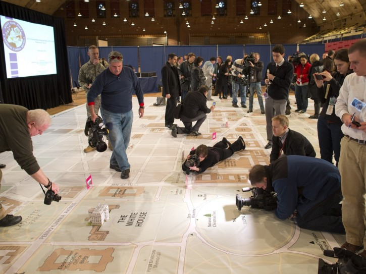News photographers take photos of a model of the White House on a giant planning map during a media tour highlighting inaugural preparations being made by the Joint Task Force-National Capital Region for military and civilian planners, at the DC Armory in Washington. (AP Photo/ Evan Vucci)