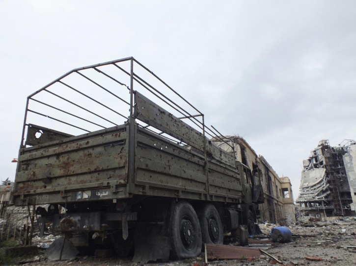 A damaged military vehicle that belonged to forces loyal to Syria's President Bashar al-Assad is seen in a damaged neighbourhood in Homs January 30, 2013. Picture taken January 30, 2013. REUTERS/Yazan Homsy