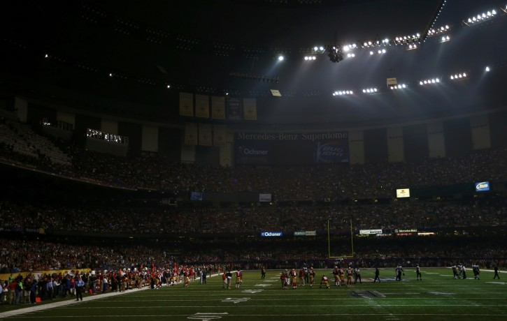 Players mill around the field after half of the lights went out during the third quarter of the NFL Super Bowl XLVII football game between the Baltimore Ravens and the San Francisco 49ers in New Orleans, Louisiana, February 3, 2013. REUTERS/Gary Hershorn